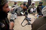 Captain John Pelikan of the 82nd Airborne gathers intelligence on the Taliban from the villagers of Kshahah Lakhchack in a remote mountain region of Kandahar province, Afghanistan on Monday, March 26, 2007.