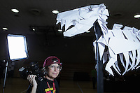 New York, NY, USA - June 24, 2011: Susan Dugan, photograher and Origami folder at the OrigamiUSA Convention in New York City standing beside a T rex created by MIT's Origami club, OrigaMIT.