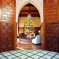 Large polished wooden doors and an ornate plasterwork archway mark the entrance to the sitting room