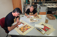 Graphic retouchers highlight the gilt painting with golden ink and then age their work with a small scalpel at the printing studio of Scriptorium SL in Valencia, Spain. Picture by Manuel Cohen