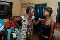 Kroo Bay, Freetown, Sierra Leone...Story on child and maternal health in the Kroo Bay slum community in Freetown, Sierra Leone, which has the World's worst infant and maternal mortalitly rates. One in 4 children die before they reach the age of 5 and one in 6 mothers dies during child birth (in the UK, the rate is one in 3,800)...The Kroo Bay Community Health Centre has a catchment area of over 8,000 people but lacks adequate facilites to provide even basic care. The clinic lacks even the basics, such as bedpans, surgical spirits and cotton wool. It has no electricity and clean drinking water must be fetched from the nearby well everyday...Sissy Aminata workshop led by Theresa Kamara (17)..Role playing a conversation between friends about HIV/AIDS with Fatmata Sesay (16), in black...© 2007 Aubrey Wade. All rights reserved.