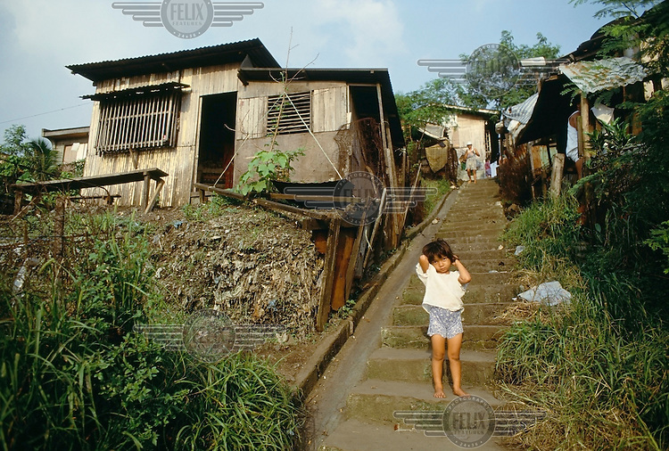 A young girl stands beside a house in the Smokey Mountain housing area. Smokey Mountain was once a two million ton landfill site where people used to scavenge for a living. Families built homes adjacent to the landfill, which later closed, forcing residents to relocate.