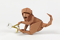 Origami monkey stealing a pair of eye glasses. Monkey designed by Akira Yoshizawa folded by Rosalind Joyce. Glasses adapted and folded by Rosalind Joyce.