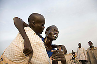 The winner of the 1500m collapses in the arms of a friend at the Twic Olympics in Wunrok, Southern Sudan.
