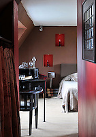 In front of the desk in this bedroom is an antique architect's chair while 19th century books from the chateau library are used as bedside tables