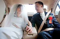 Caroline and San hold hands in the car while travelling to their tea ceremony and wedding celebration in Seattle. (Photo by Dan DeLong/Red Box Pictures)