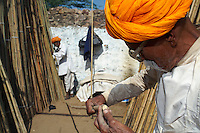 Two elderly Rajasthani Men looking for the right Bamboo stick from an open shop during the Pushkar Camel Fair, Rajasthan.