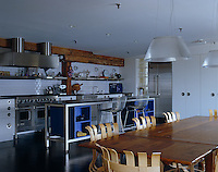 An extendable dining table dominates this kitchen/dining room which is decorated in white and stainless steel
