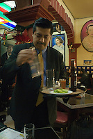 A waiter serves drinks inside the popular Tenampa bar in Plaza Garibaldi where Mariachis gather to be hired in Mexico City, Friday, Jan. 4, 2008