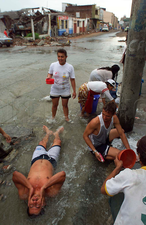 1/28/99 AL DIAZ/HERALD STAFF--Bathing in the streets of Armenia at a broken water main is Jesus Marie Geraldo, as others wash their clothes. They are victims from Monday's earthquake in Colombia.