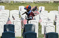 A boy carries American flags as he pass by a soldier's grave before the memorial day commemorations at the Cypress Hill cemetery in New York City, United States 05/23/2015. Kena Betancur/VIEWpress