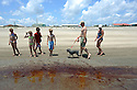 A family walks along the public beach just before officials closed the beaches as oil washed on shore at Grand Isle, La., Friday, May 21, 2010.