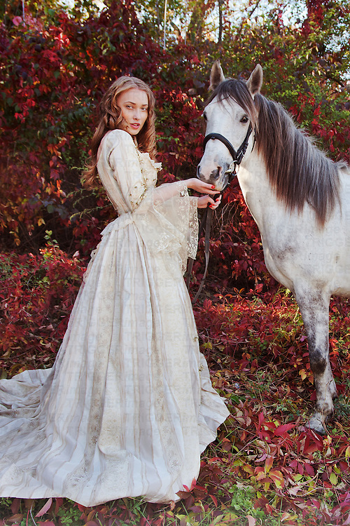 Young woman with blonde hair wearing period costume standing outdoors beside white horse