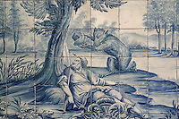 The bear and the gardener, with the bear about to kill the fly and man with a rock, from the fables of La Fontaine, traditional blue and white azulejos tile scene, 18th century, in the cloister of the Monastery of Sao Vicente de Fora, an Augustinian order monastery and church built in the 17th century in Mannerist style, Lisbon, Portugal. The monastery also contains the royal pantheon of the Braganza monarchs of Portugal. Picture by Manuel Cohen
