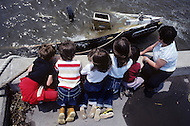 Ile D'Orleans, Quebec City Area, Canada, June 8, 1984. Kids watching a sank boat in the Saint Laurent River.