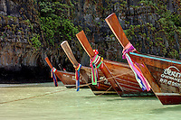 Long tail boats rest in the emerald waters of Maya Bay, Koh Phi Phi, Thailand.