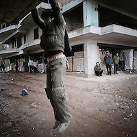 A young refugee jumps down from the first floor of the building where he is squatting. Patras is home to about 3,000 illegal immigrants. Most of them are Afghans, although there are also some Iranians and Uzbeks. They stop in Patras to try and find passage to various European destinations by hiding in ships, containers and trucks parked in the port. If they are lucky they will make it to their destination. Many of them live in shacks made from cartons, plastic and wood they found on the beach. To shelter from the cold they also squat in abandoned buildings, living without water and electricity. The living conditions are inhumane and unhygienic.
