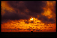 SUNRISE OVER UPPER HARBOR BREAKWATER LIGHT IN MARQUETTE MICHIGAN WITH CLOUDS.