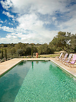 A terracotta figure stands at one end of the long swimming pool set in the Majorcan countryside