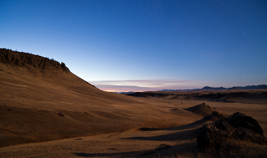 Pastel colors creep above the horizon during the twilight hours between night and dawn in Cascade County, Montana near Crown Butte.