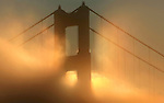 The sunrise lights up the fog as it streams through the northern tower of  Golden Gate Bridge on the last day of the year 2008 as seen from the Marin Headlands on December 31, 2008.