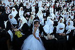 Palestinian brides take part in a mass wedding ceremony in Gaza City, on May 31, 2015. Nearly 2000 Palestinian couples were married in a ceremony funded by the Turkish government and supported by the Hamas movement. Photo by Ashraf Amra
