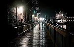 Hard rain dampens the wooden boards of Historic Wilmington's Riverwalk along the Cape Fear River.  Sometimes, just after a hard shower, as light reflects from street lamps lost soul's emerge for a brief moment in time.  Photo By:  Jeff Janowski Photography