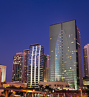 Vertical panorama showing several office buildings and condos on and adjacent to Miami's Brickell Avenue at night.