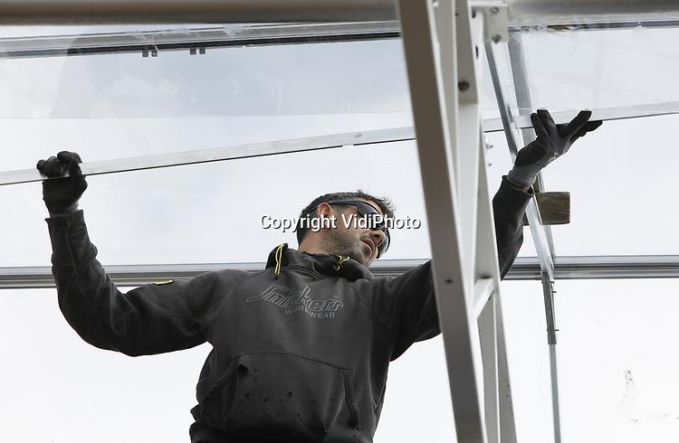 Foto: vidiPhoto<br /> <br /> BEMMEL - In het kassengebied Bergerden bij Bemmel Gelderland wordt donderdag door Maurice Kassenbouw BV het glas geplaatst voor een enorme aardbeienkas van 6 ha. De uitbreiding is van Royal Berry, de grootste aardbeienteler van Gelderland. Nadat vorig jaar al een extra aarbeienareaal van 7,5 ha. onder de kap is gerealiseerd, wordt op dit moment gebouwd aan weer een nieuwe kas. Het totale aardbeienareaal van Royal Berry komt daarmee op 25 ha. De vraag vanuit zowel binnen- als buitenland naar kwaliteitsaarbeien is zo groot, dat er ruimte is voor het vergroten van de productie. Ruim 90 procent van de aardbeien van Royal Berry gaat naar het buitenland. Met name in Duitslands zijn Hollandse aardbeien enorme populair.