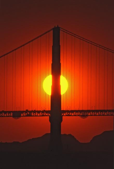 Sun sets behind Golden Gate bridge