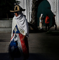Medina, Tangier, Morocco pictured on December 27, 2009. A woman in traditional costume and cardigan walks confidently past an elaborate gateway in the Old Town, her straw hat and veil shading her from the sunshine. Tangier, the 'White City', gateway to North Africa, a port on the Straits of Gibraltar where the Meditaerranean meets the Atlantic is an ancient city where many cultures, Phoenicians, Berbers, Portuguese and Spaniards have all left their mark. With its medina, palace and position overlooking two seas the city is now being developed as a tourist attraction and modern port. Picture by Manuel Cohen