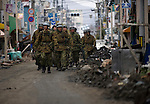 Japan Self-defense force troops make their way down  Manga-dori shopping steet in Ishinomaki, Miyagi Prefecture, Japan on 15 March, 2011. Badly affected byt the March 11 tsunami, some stores along the street were preparing to open one month later..Photographer: Robert Gilhooly