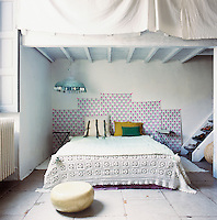 The bedroom has a simple, rustic feel with its painted roof beams and stone floor. A crochet cover adorns the bed