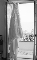 wedding dress hanging in a doorway in Italy