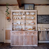 A distressed wooden dresser in the kitchen displays a collection of ironstone transferware and apothecary jars