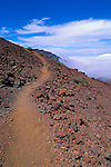 Trail through lava field above a sea of clouds in Haleakala Crater, Haleakala National Park, Island of Maui, Hawaii