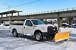 Merrick, New York, USA. January 24, 2016. After Nor'easter drops more than two feet of snow on south shore if Nassau County, Long Island, many Town of Hempstead employees operate snow plows, including 4X4 truck with blade attached, to remove about 25 inches of snow blanketing downtown streets and public parking lots for the Merrick Long Island Railroad LIRR station.