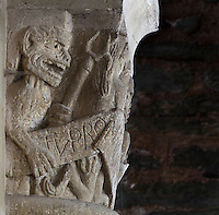 Carved capital depicting a demon with his fork and a phylactery, in the North transept of the Abbatiale Sainte-Foy de Conques or Abbey-church of Saint-Foy, Conques, Aveyron, Midi-Pyrenees, France, a Romanesque abbey church begun 1050 under abbot Odolric to house the remains of St Foy, a 4th century female martyr. The church is on the pilgrimage route to Santiago da Compostela, and is listed as a historic monument and a UNESCO World Heritage Site. Picture by Manuel Cohen
