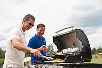 Two men preparing food on a barbecue