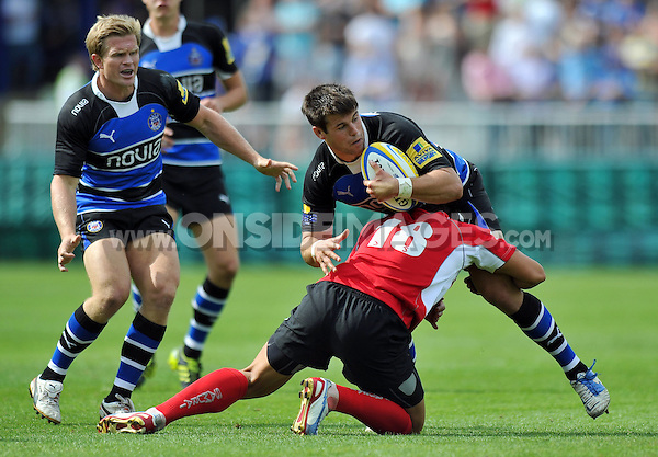 Guy Mercer is tackled by Gavin Henson. Pre-season friendly match, between Bath Rugby and London Welsh on August 11, 2012 at the Recreation Ground in Bath, England. Photo by: Patrick Khachfe / Onside Images