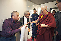 "Switzerland. Basel. St. Jakobshalle. Rinzin Lang (L) and Thubten Purang (C) greet and pay tribute to His Holiness the Dalai Lama. They offer him scarfs, called khata, with a humble bow before them. In most cases the giver will receive his or her Khata back from the given, as a token of blessing back to them. When a Khata is offered to His Holiness the Dalai Lama and received back, it will be cherished and preciously kept as it is now a very special blessing, a talisman and protector. The two men are part of Aeschimann's children who arrived 50 years ago in Switzerland to receive custody on a private initiative by an influential Swiss industrialist, Charles Aeschimann. In 1962, Charles Aeschimann agreed with the Dalai Lama to take 200 children and place them in Swiss foster homes and give them a chance for a better life and a good education. Most of the children still had parents in exile or in Tibet, just a few were orphans. The 14th and current Dalai Lama is Tenzin Gyatso, recognized since 1950. He is the current Dalai Lama, as well as the longest-lived incumbent, well known for his lifelong advocacy for Tibetans inside and outside Tibet. Dalai Lamas are amongst the head monks of the Gelug school, the newest of the schools of Tibetan Buddhism. The Dalai Lama, also called "" Ocean of Wisdom"" is considered as the incarnation of Chenresi, the Bodhisattva of compassion who is also the protective deity of Tibet. 8.02.2015 © 2015 Didier Ruef"