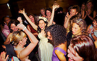 A bride rejoices with girlfriends before getting married at Mills College, CA.