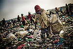 Life at Steung Meanchey, the landfill outside of Phnom Penh, the Capitol of Cambodia, where many people making a meager wage of $1 US dollar per day or less collecting recyclables from the trash. Families live on or near the smoking rubbish heaps and represent some of the disadvantaged and vulnerable to exploitation in a post-conflict country with a limited middle class.