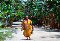 Woman walking down the main street of Tuvalu, South Pacific