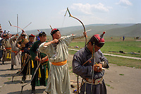 Ulaanbaatar, Mongolia, July 2003..Competitors in the archery contests in the national Naadam at Ulaanbaatar central stadium. An archer releases his arrow while another makes a note of his score on his hand.