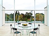 The dining room is set within a glass cube and has a large round glass table at its centre