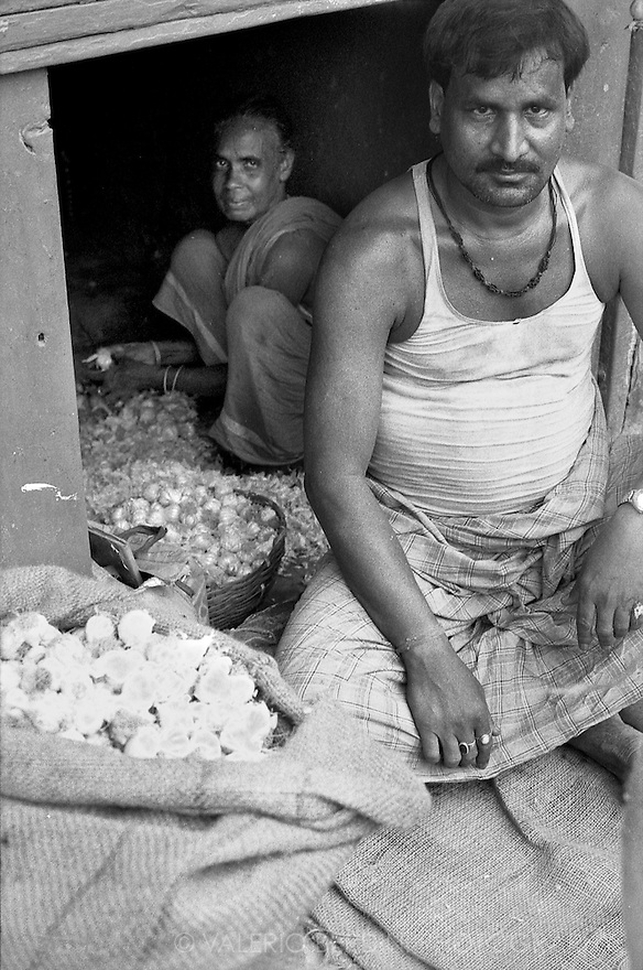 Husband and wife peeling and selling garlic bulbs
