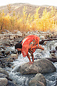 Woman outdoors in yoga pose bakasana in a mountain river.