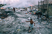 Children play among the detritus of a rubbish dump. Children and many unemployed adults often go to the dump in search of any discarded items that they can use. Previously the land was used as a softball field, but lately the local authorities decided to move it to one of the neighbouring islands immediately to the north of Ebeye that are connected with the island by causeway.
