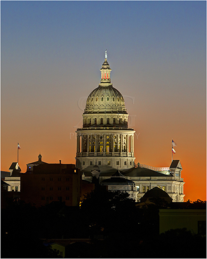 Taken from west of the University of Texas campus, this view shows the state capitol building in Austin as daylight begins to turn the sky orange and blue in the morning hours before sunrise.